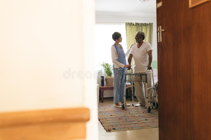 Female nurse talking with senior man while walking with walker stock images