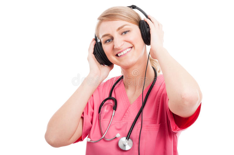 Female nurse wearing scrubs listening to headset. Female nurse wearing scrubs listening music on headset and smiling isolated on white background with copy text stock photos