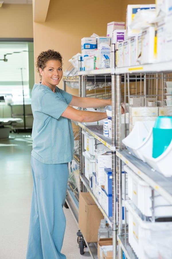 Female Nurse Working In Storage Room. Side view portrait of female nurse smiling while working in storage room of hospital stock image