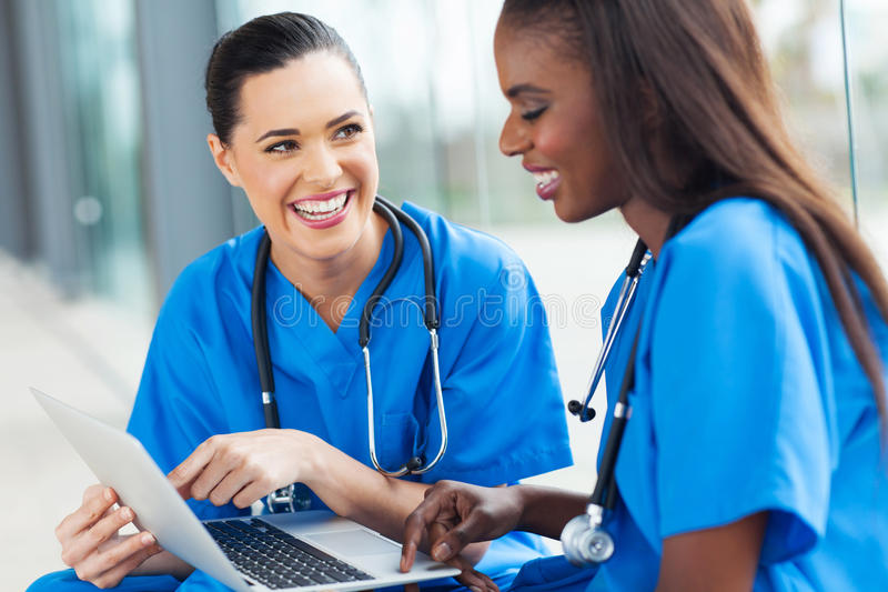 Female nurses fun. Beautiful young female nurses having fun with laptop