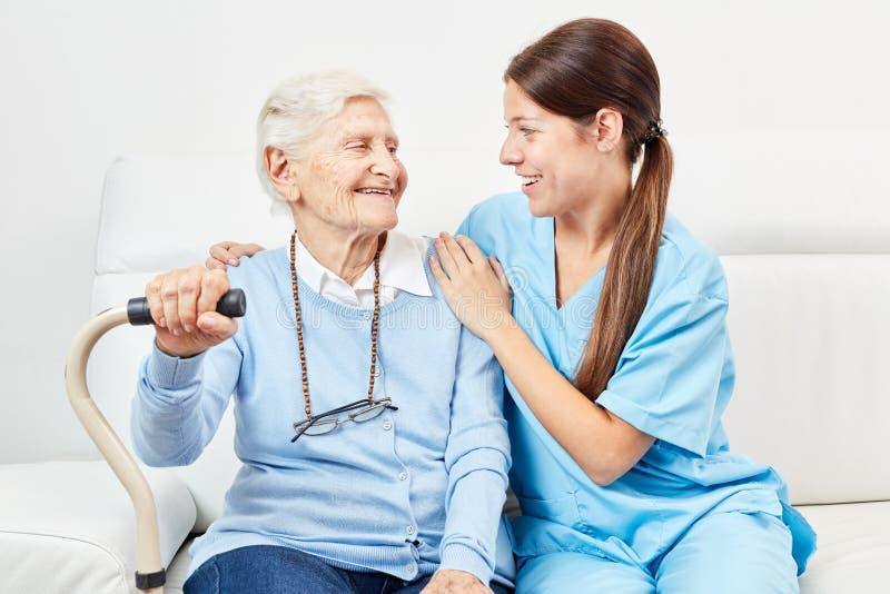 Female nursing assistant and happy senior citizen stock photography
