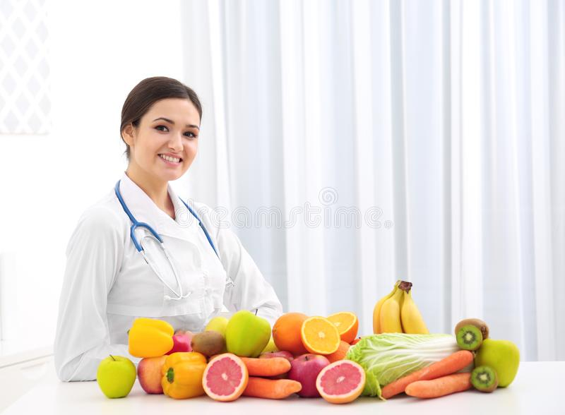 Female nutritionist with different fruits and vegetables. At desk royalty free stock images