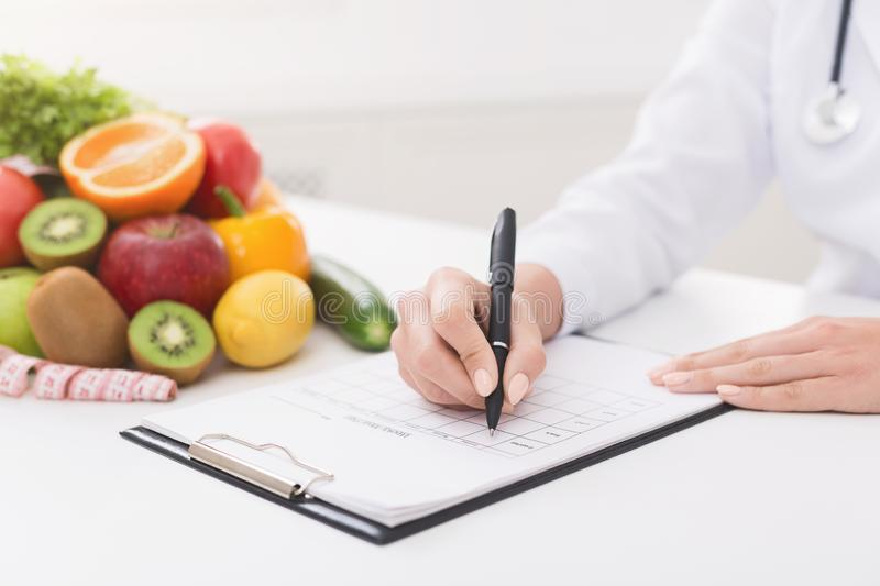 Female nutritionist doctor writing vegetable diet plan royalty free stock photography