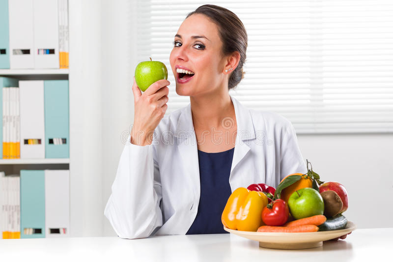 Female nutritionist eating a Green Apple in her office royalty free stock photo