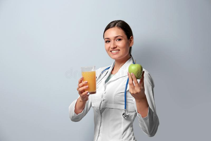 Female nutritionist with glass of juice and apple stock image