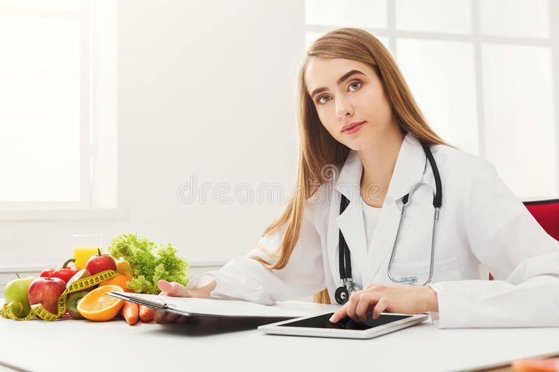 Female nutritionist working on digital tablet royalty free stock photography