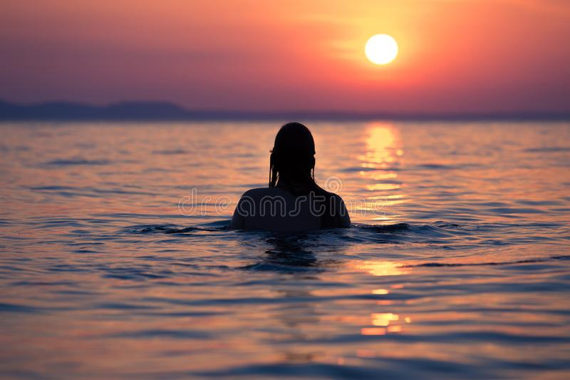 Female in ocean at sunset royalty free stock image