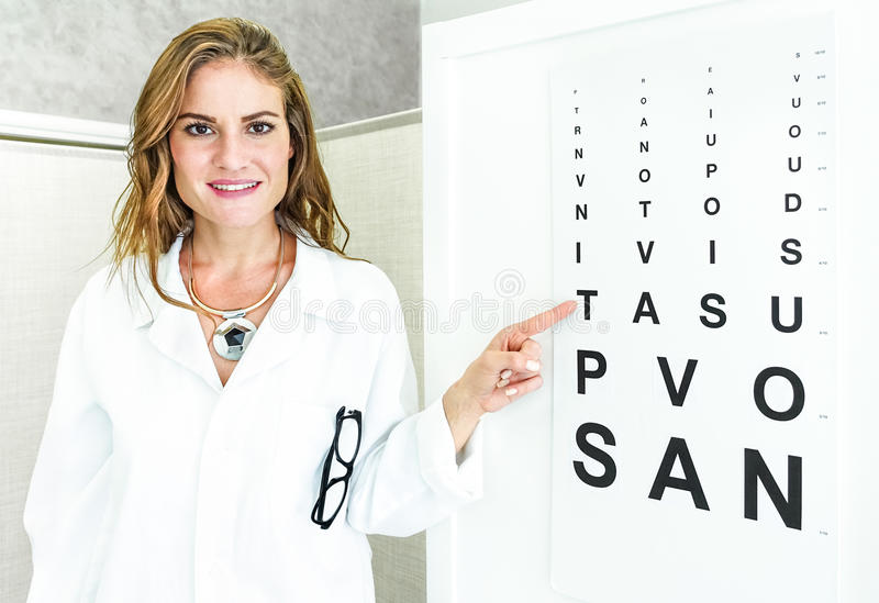 Female oculist doctor pointing at eye sight test chart. And looking at camera - Optic medical concept in private clinic studio with young woman welcoming and stock image
