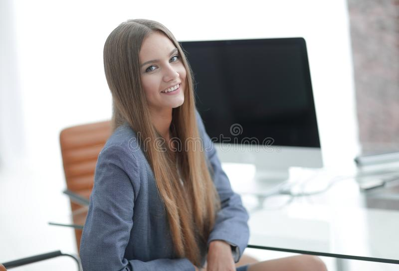 Female office employee sitting at a Desk. Portrait of young female office employee sitting at a Desk royalty free stock photo