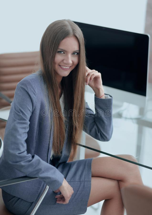 Female office employee sitting at a Desk. Portrait of young female office employee sitting at a Desk stock image