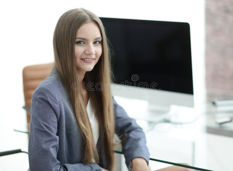 Female office employee sitting at a Desk. Portrait of young female office employee sitting at a Desk stock images