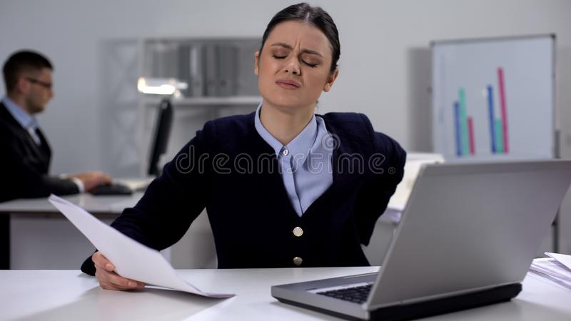 Female office manager feeling lower back pain on workplace, sedentary lifestyle. Stock photo royalty free stock image