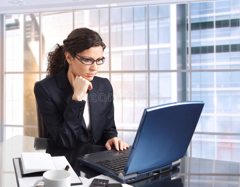 Female Office worker. Young female office worker sits in front of her computer screen. Daylight, indoor, office. Dark cloth