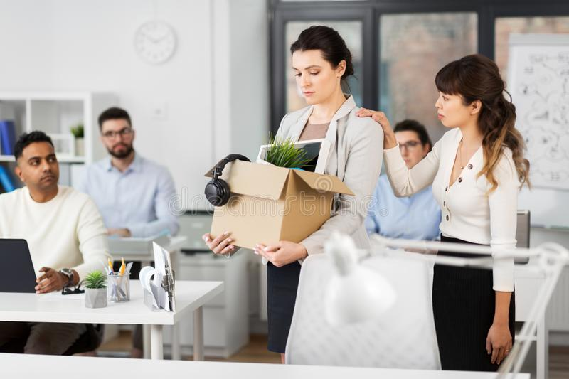 Female office worker with box of personal stuff royalty free stock image