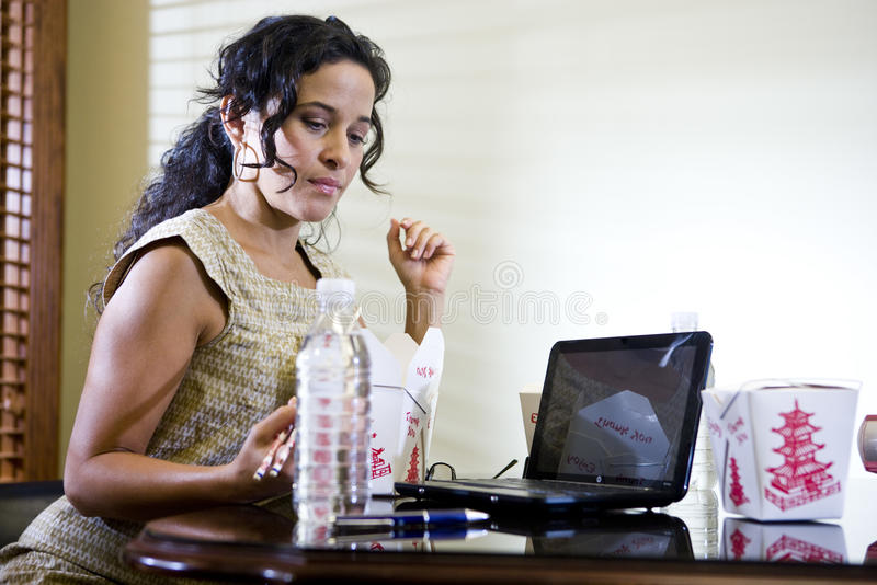 Female office worker eating takeout working on la. Female Hispanic office worker eating Chinese takeout food for lunch while working on laptop royalty free stock image