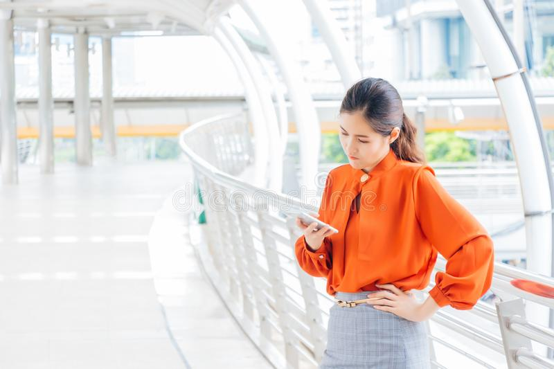 The female office worker is frustrated that the boyfriend is coming late. There is a high-rise building in the outdoor stock images