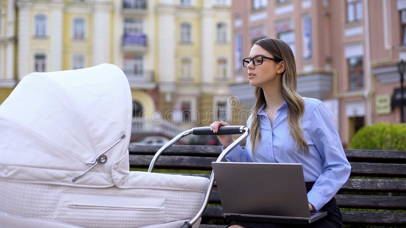 Female office worker preparing report on laptop and taking care newborn in pram royalty free stock photography