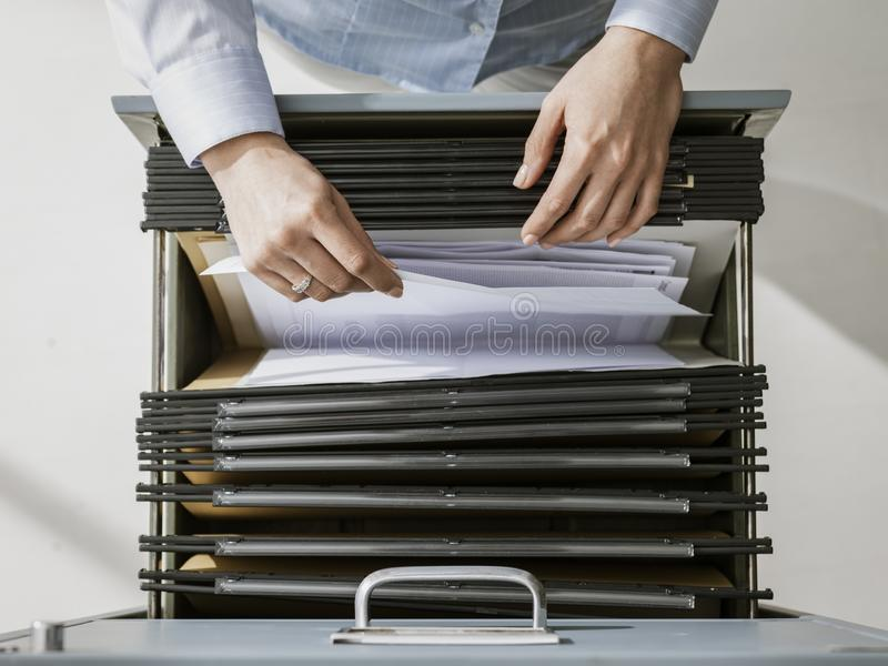 Office worker searching files in the archive stock image