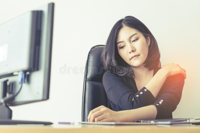 Female office worker suffering injury on shoulder from long hour of work royalty free stock image