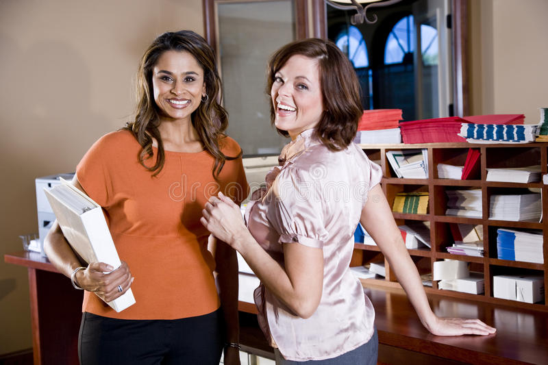 Female office workers chatting in copy room royalty free stock images