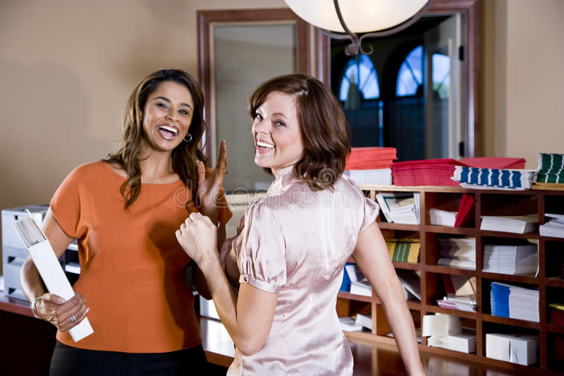 Female office workers chatting in copy room stock photos