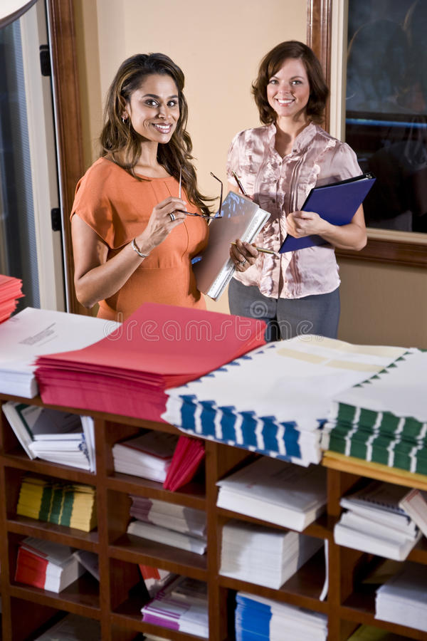 Female office workers standing in mailroom stock photography
