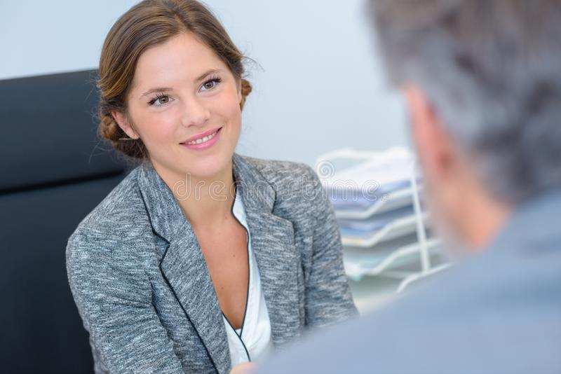Female office workers talking and smiling stock image