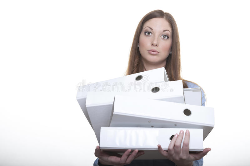 Female officer carries stack of folders. Long haired brunette female officer carries a stack of white folders tands in front of white isolated background looking stock images
