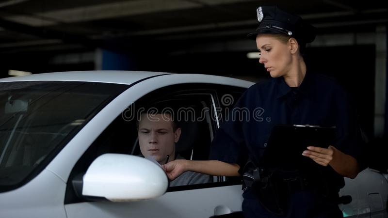 Female officer giving traffic ticket to male driver for parking violation, fine royalty free stock images
