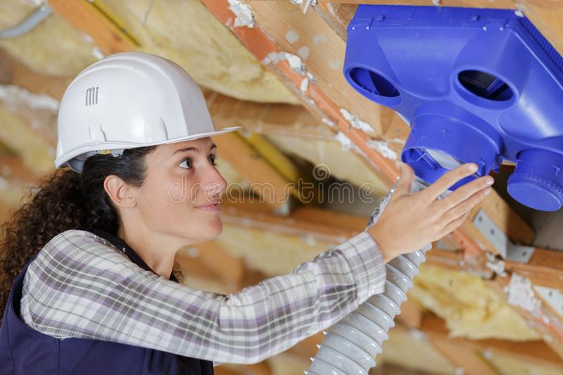 Female operator inspecting air conditioning pipes stock photo
