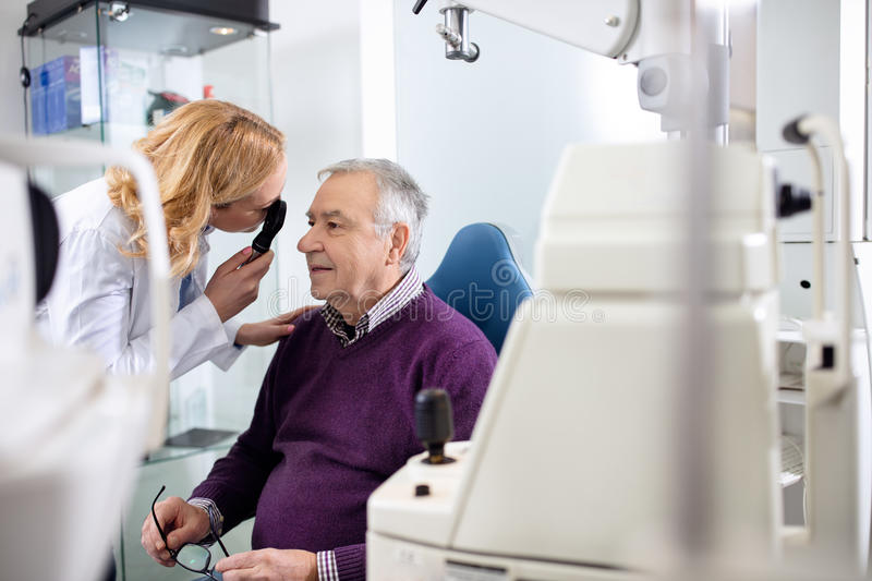 Female ophthalmologist determines diopter. To elderly man stock image