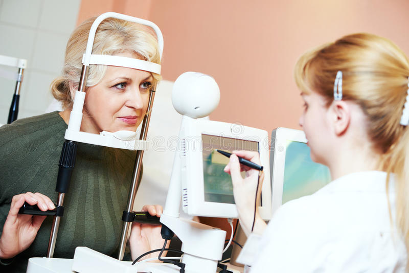 Female ophthalmologist or optometrist at work. Optometry concept. female optometrist optician doctor examines eyesight of female patient in eye ophthalmological stock images