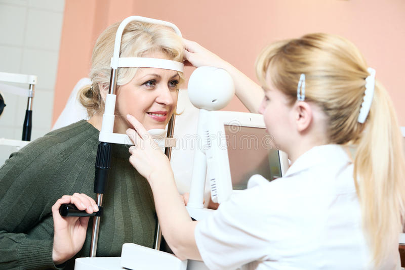 Female ophthalmologist or optometrist at work. Optometry: female optometrist optician doctor examines eyesight of female patient in eye ophthalmological clinic stock photography