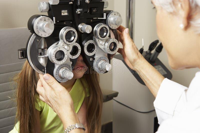 Female Optician In Surgery Giving Girl Eye Test stock photos