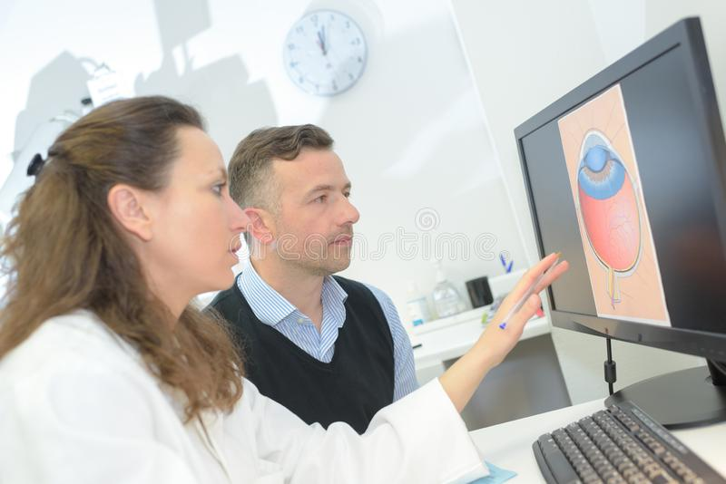 Female optometrist showing eye draft to male patient royalty free stock photography