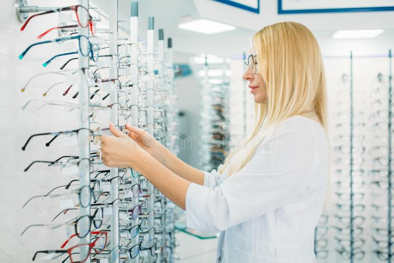 Female optometrist shows glasses in optics store royalty free stock images