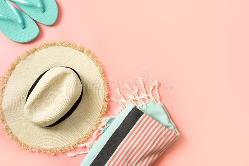 Female outfit for beach. Straw sunhat and beach slaps on punchy pink with space for text. Summer concept royalty free stock image