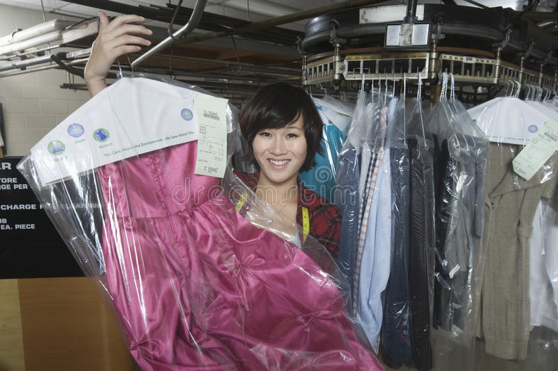 Female Owner Displaying Clean Dress In Laundry. Portrait of happy female owner displaying clean dress in laundry royalty free stock photography
