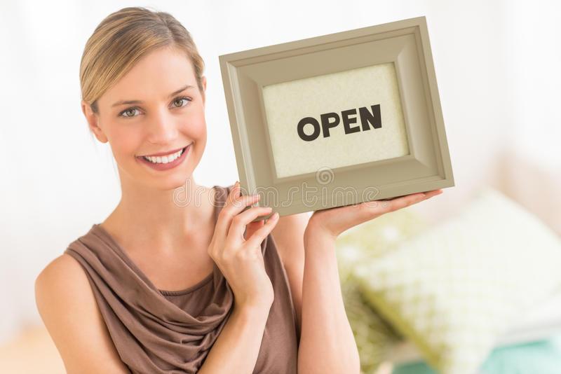 Female Owner Holding Framed Open Sign In Bedding Store. Portrait of beautiful female owner holding framed open sign in bedding store stock images