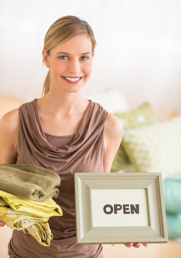 Female Owner Holding Sheets And Open Sign In Bedding Store. Portrait of young female owner holding sheets and framed open sign in bedding store royalty free stock images