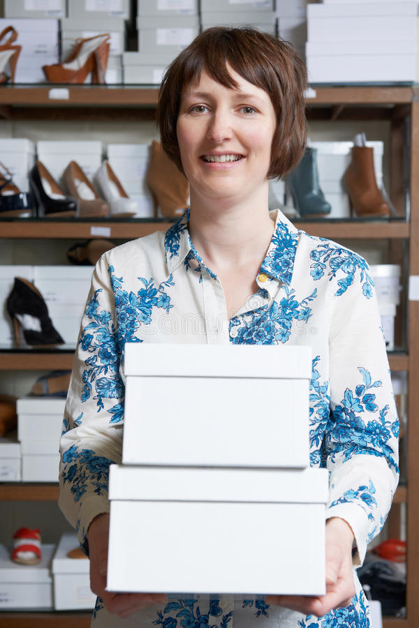 Female Owner Of Shoe Store Carrying Boxes royalty free stock photography