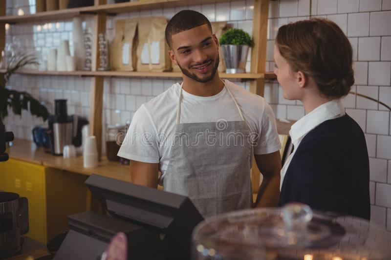 Owner talking with waiter in cafe stock photography