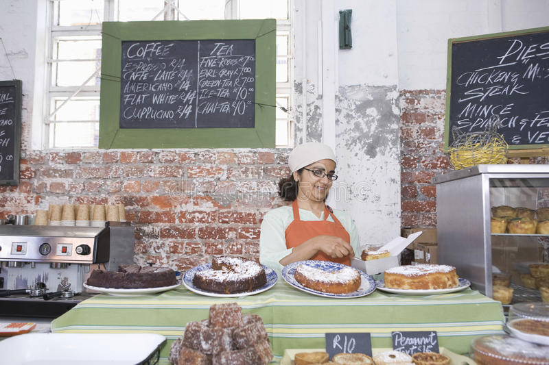 Female Owner Working At Counter. Middle aged female owner working at counter in cake shop stock image