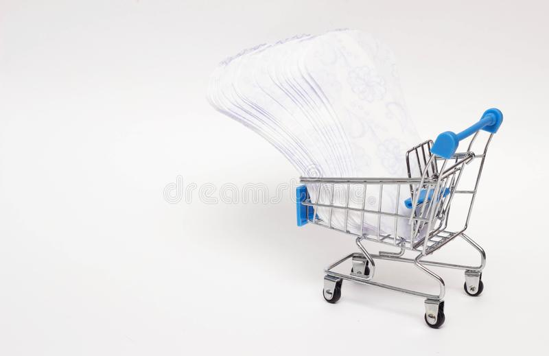 Female pads in a shopping trolley on a white background, personal hygiene shopping concept, close-up, copy space. Female pads in a shopping trolley on a white stock image