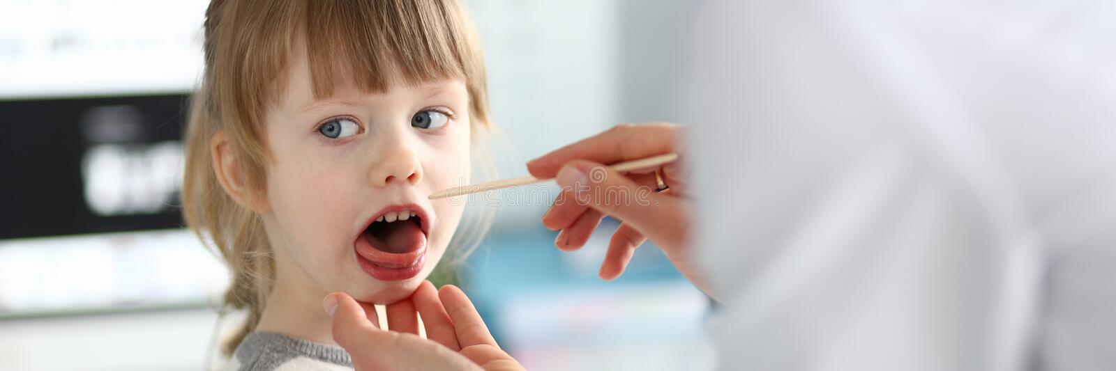 Female paediatrician examining little kid patient throat with wooden stick royalty free stock photo