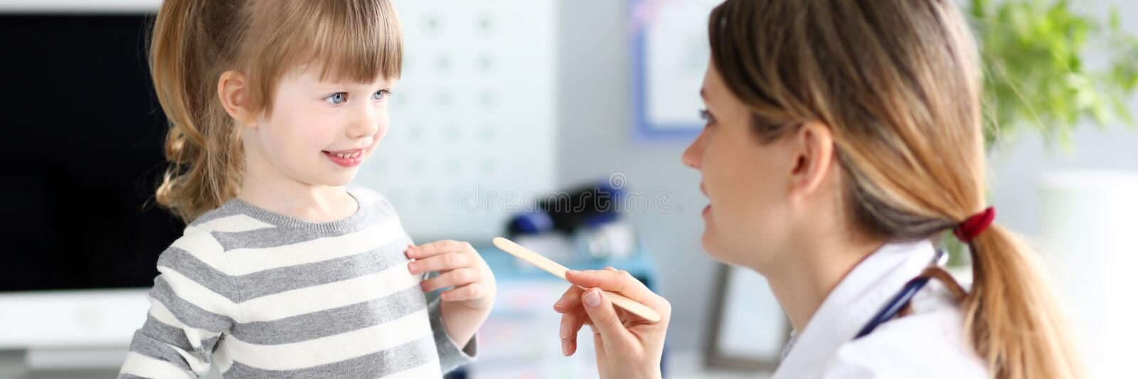 Female paediatrician examining little kid patient throat with wooden stick stock photos