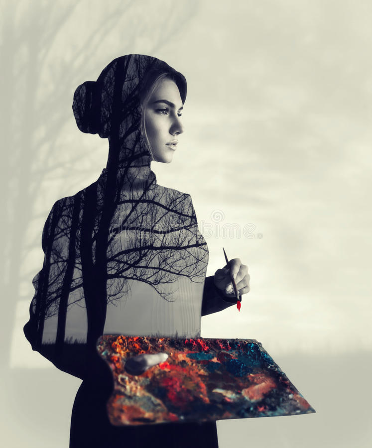 Female painter, double exposure effect. Female painter with brush and palette in hands, body with forest texture, double exposure. Woman on blur background royalty free stock photos