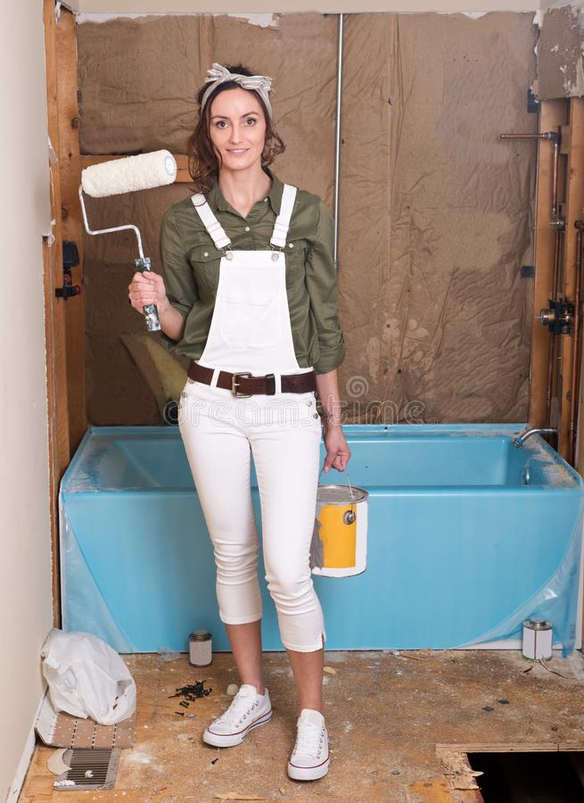 Female painter holding painting roller and bucket of paint royalty free stock images