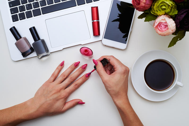 Female painting her nails in pink royalty free stock photo