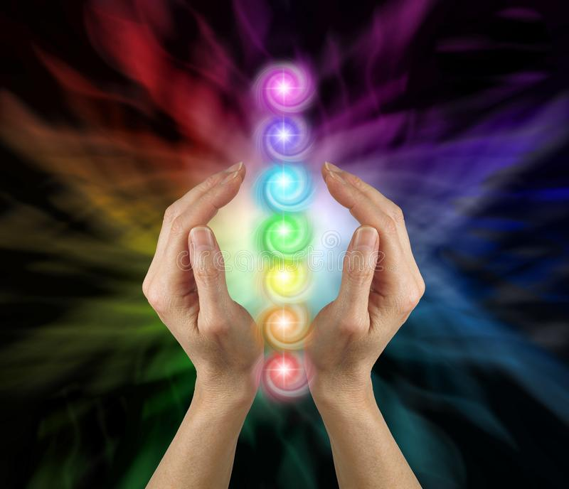 Sending the Seven Chakras Vortex Healing Energy. Female parallel hands against a multicoloured background of energy and the Seven Chakras floating between her stock illustration